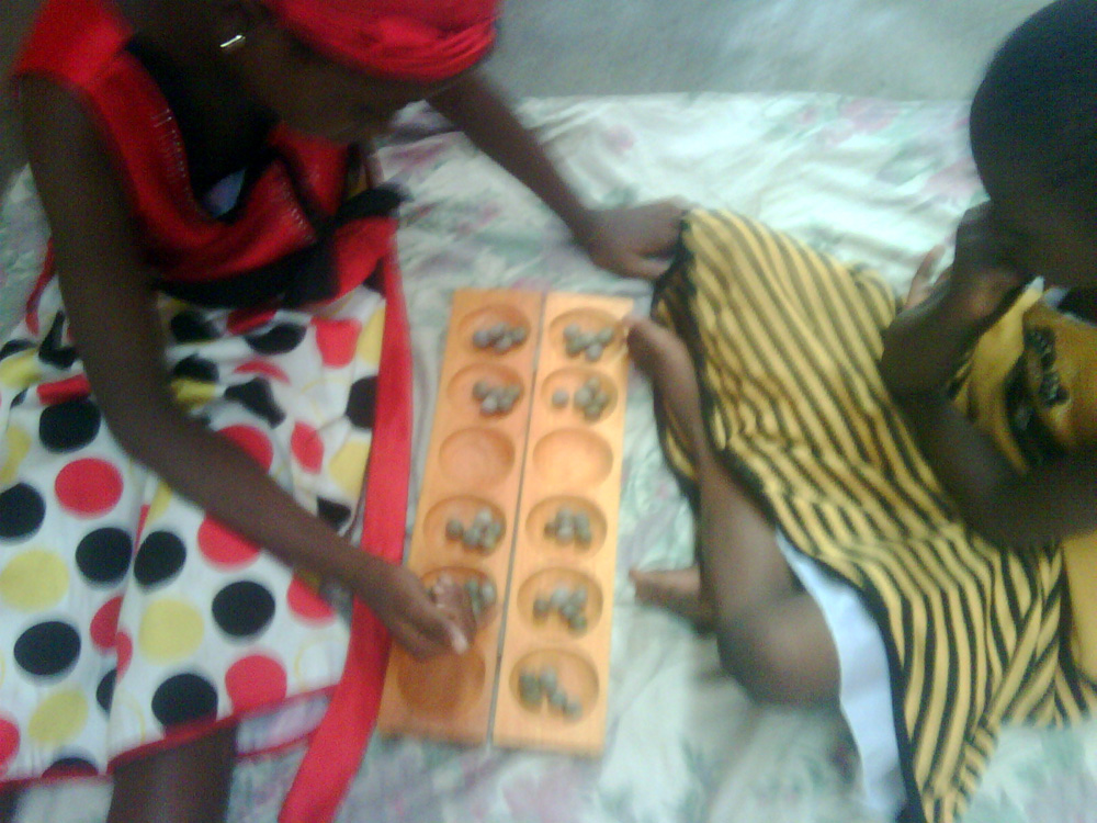 photos showing my 2 daughters playing the ancient board game of Ayo